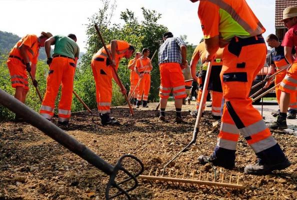 Anlagetag Juli 2018. Auf einer Neuanlagefläche arbeiten Bauhofmitarbeiter Kompost in den Kies ein