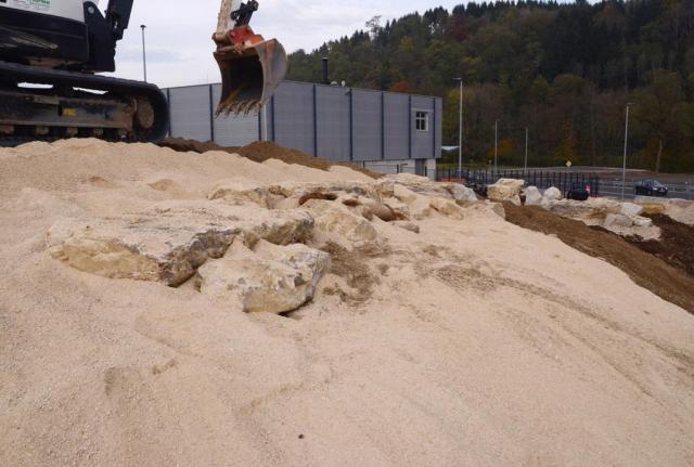 Über die Steinriegel wirft der Bagger große Mengen feinsten Sandes, so entsteht der künftige Trockenhang