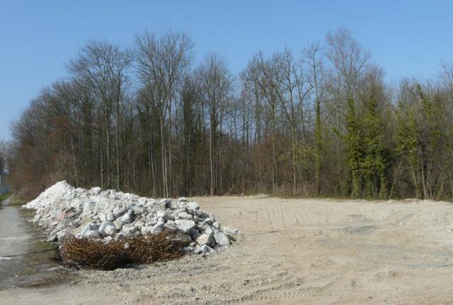 Nach dem Abriß liegt der zerkleinerte Bauschutt am Rand, die Restfläche ist eine große Kiesebene.