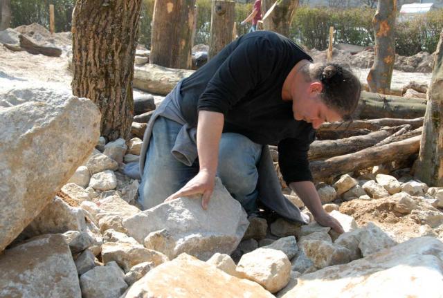 Zwischen aufrecht stehenden und liegenden Holzstämmen befinden sich mit Steinen aufgeschüttete Bereiche. Sorgsamer Einbau von großen Kalksteinen als Unterschlupf für Eidechsen.