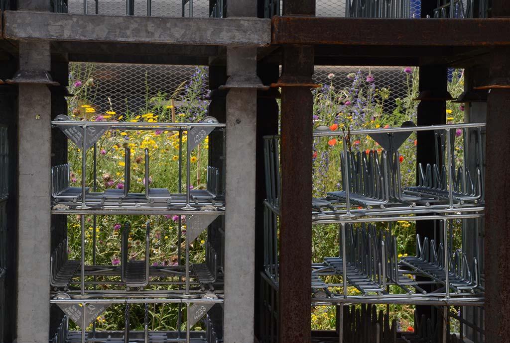 Durch Metallcontainer sieht man bunte Blumenpracht. Das ist das Bild für die Symbiose von Natur & Wirtschaft. Es geht beides. Wir haben so viel Flächen in Firmengeländen