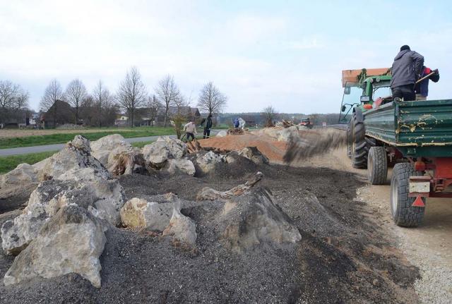 Grobe Felsbrocken liegen entlang eines Weges, eingebettet in sehr viel Sand. Bau des 150 Meter langen Steinriegels, ein typisches Element der oberfränkischen Kulturlandschaft