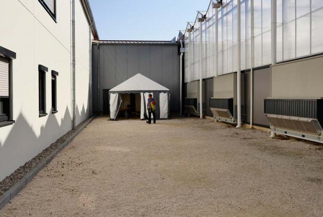 Blick auf Kalkschotterfläche zwischen Gebäuden. Vorher-Bild des Pausenbereiches. Bisschen langweilig, keine Natur, nur technische Räume