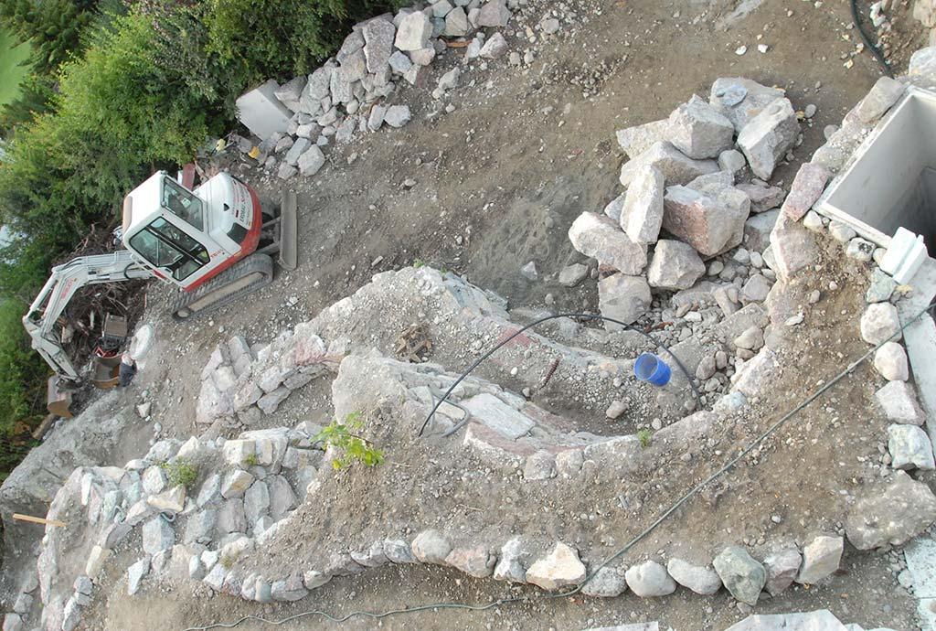 Man sieht von oben auf eine Bastelle mit zum Teil fertigen Mauern und Beeten. Es liegen aber auch noch viele Steine und Kies herum. Blick von oben auf Treppen, Wege und Beete. Von unten nach oben sind es an dieser Stelle 3 m Höhenunterschied