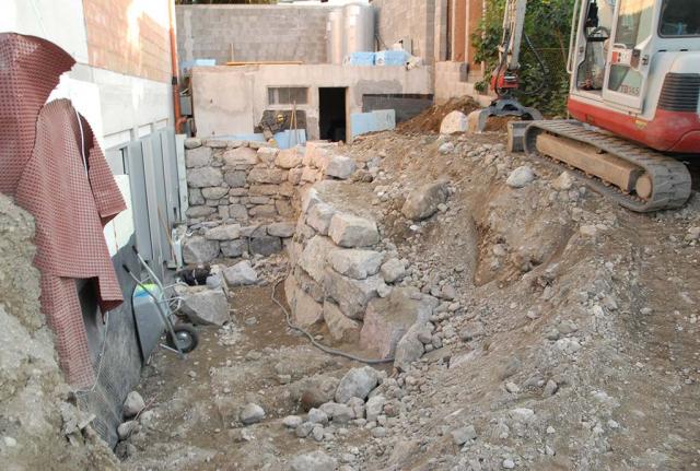 Trockenmauerbau mit großen Natursteinen hinter dem Haus. Die Grundstücksbreite beträgt hier 7 m. alles ist sehr eng., auf einer höheren Ebene steht sogar noch ein Bagger