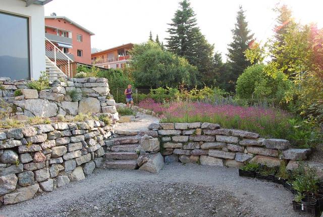 Diffenzierter Garten mit vielen durch Trockenmauern abgefangenen Beete und Ebenen, dazwischen verbindende Natursteintreppen. Ganz unten ins Loch soll noch ein Schwimmteich rein, der Rest ist fertig. Hohe und höchste Trockenmauern aus Inntal-Kalkstein.