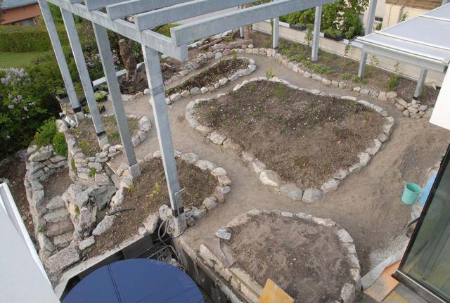 Blick von oben auf die Carportbegrünung. Von einreihigen Trockenmauern umgebene und erhöhte Beete in organischen runden Formen, nach unten gehen Treppen ab