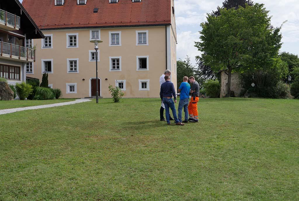 Vier Leute stehen auf einer Wiese. Erstbegehung in Fridolfing. Die große Rasenfläche vor dem Rathaus bietet sich besonders an. Ein prominenter Platz für die Idee