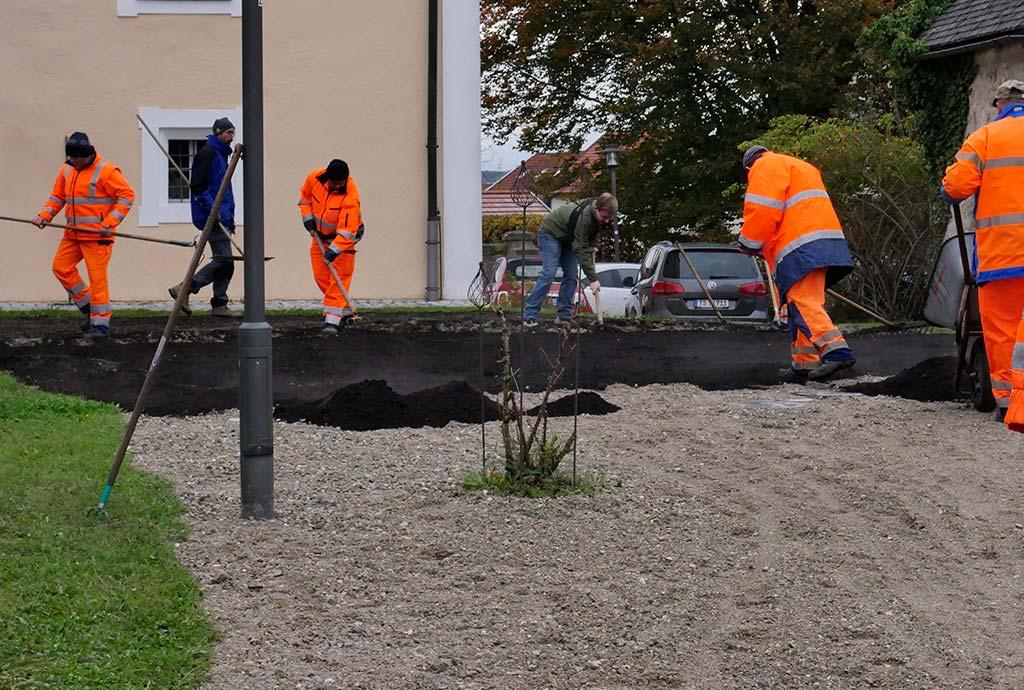 Der Rasen ist weg, jetzt liegt Kies auf der Fläche. Erster Workshop mit dem Bauhoftraining. Die Bauhofleute tragen auf der Rathauswieseden Kompost auf