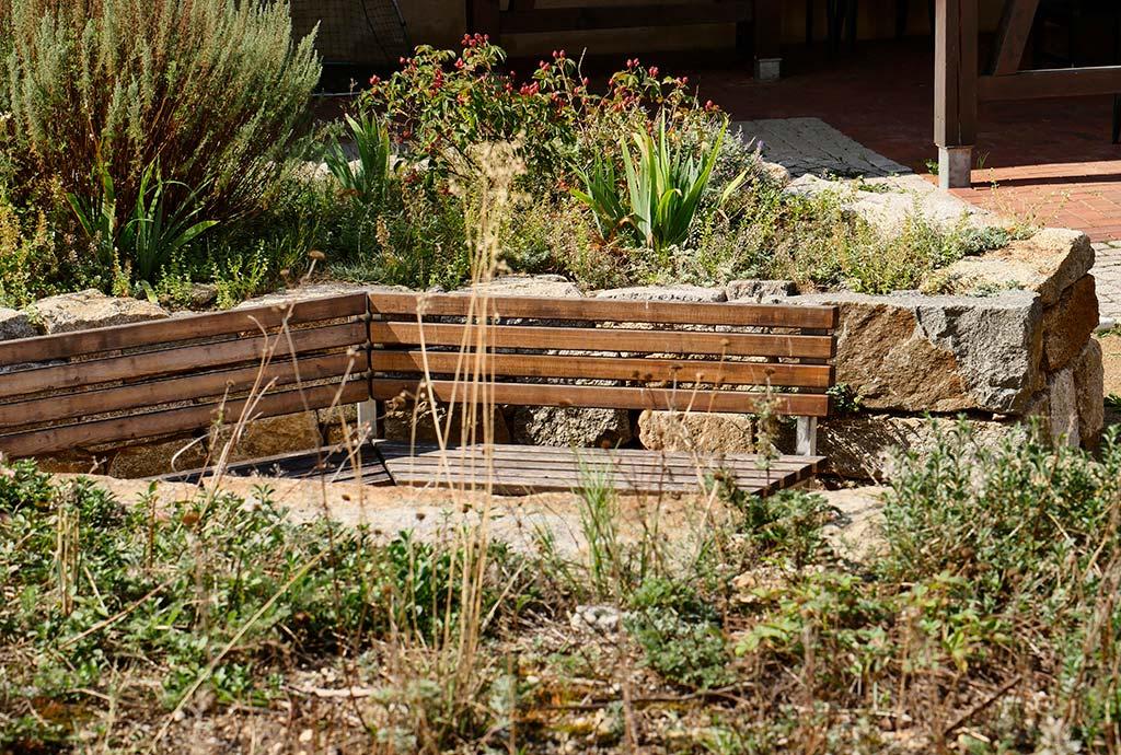 Der Sitzplatz in Herbststimmung 2018. Auf den Beeten drumherum trockene braune Stengel und ab und zu dazwischen noch gruene Blaetter. Die Rosen tragen fette rote Hagebutten