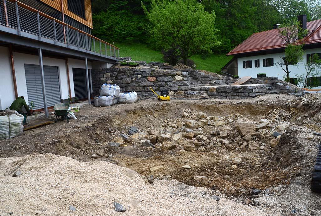 Vorne noch Baugrube, bald mit Wasser gefüllt. Im Hintergrund wurde schon eine 2, 5 m hohe Trockenmauer aus maechtigen Kalksteinen erbaut.