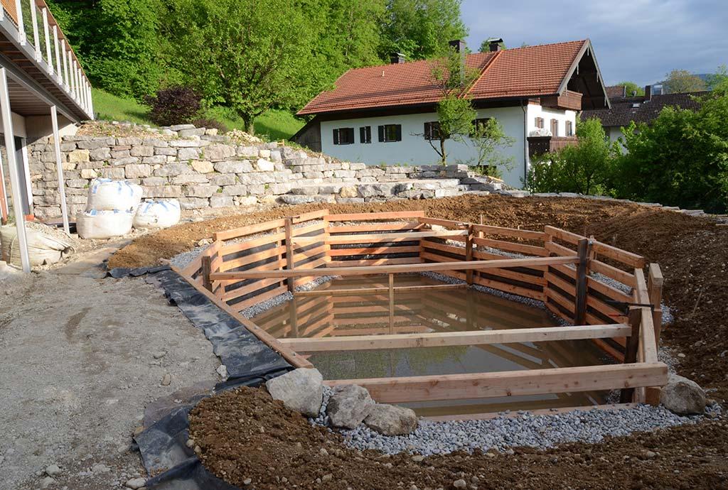 Die Geschichte schreitet voran. Das Haltegeruest aus Laerchenholz steht schon im Schwimmteich. Das Rosen-Duftpflanzenbeet ueber der Mauer ist bepflanzt.