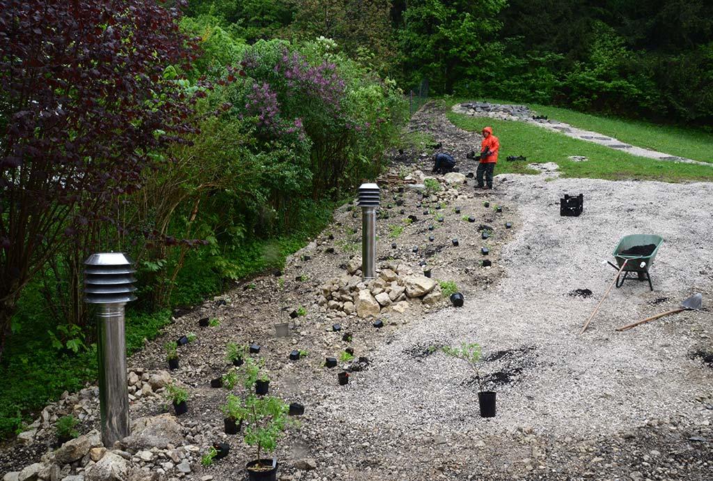 Man sieht Kiesflaechen mit ausgelegten Wildstauden und Gehoelzen. Am Grundstuecksrand wird auf unkrautfreiem Boden ein neuer Wildblumensaum etabliert.