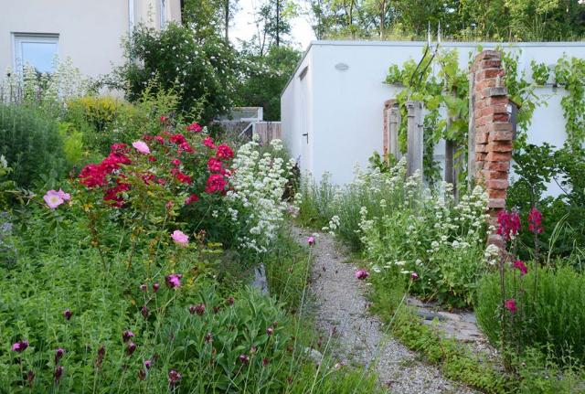 Gemüsegarten rechts mit gemauerten Backsteinfragmenten, links die üppig blühenden Rosen-Duftpflanzenbeete