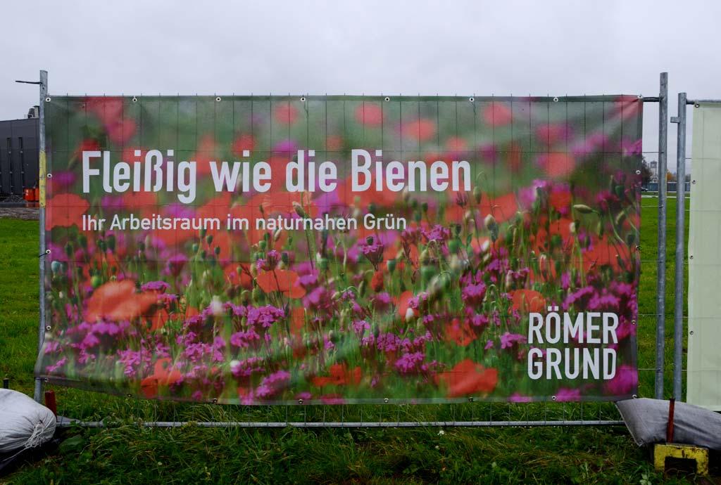 Auf einem Schild steht. Fleißig wie die Bienen. Ihr Arbeitsraum im naturnahen Grün. Das Gewerbegebiet Römergrund ist das erste naturnahe Betriebsgebiet in Europa.