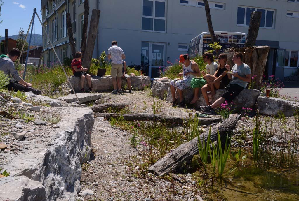 Bild vom fertigen Naturteich mit herumsitzenden und essenden Leuten. Hier treffen sich die Mitarbeiter oft zur Pause