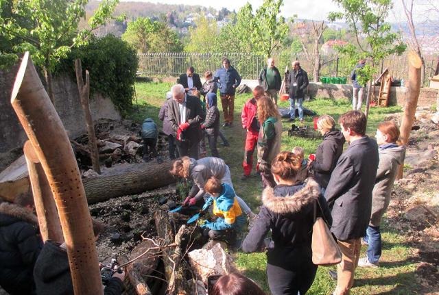 Ministerpraesident Winfried Kretschmann bepflanzt zusammen mit Kindern einen  Artenschutzbereich. Man sieht Kiesflächen, aufrechte undliegende Holzstaemme und viele Menschen (Foto: Staatsministerium)